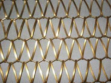 A piece of brass conveyor belt mesh on the gray background.