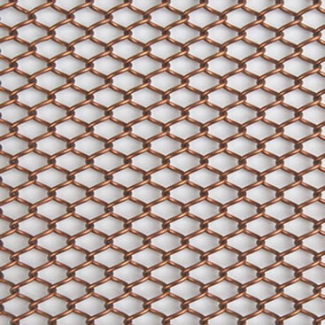 A piece of copper metal coil drapery on the gray background.