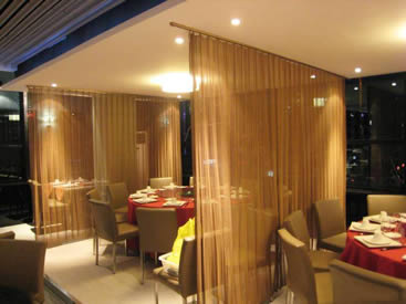 Two pieces of metal coil draperies are installed as the space divider in the restaurant.