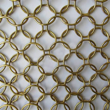 A piece of brass chain braided metal ring mesh on the gray background.