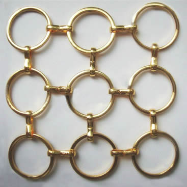 A piece of brass S hook metal ring mesh with round wire on the gray background.