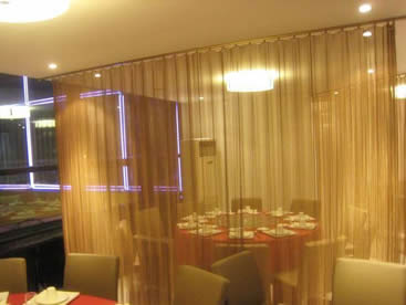 Brass metal coil drapery is installed in the restaurants to divide two tables.